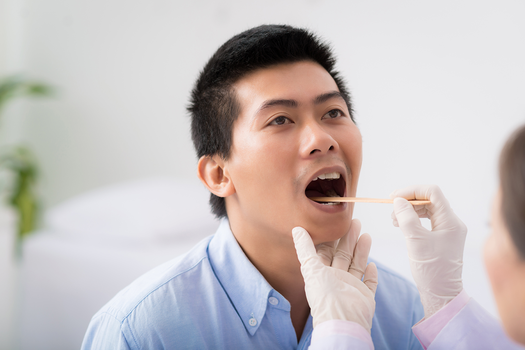 ENT Doctor examining throat of patient with tongue depressor