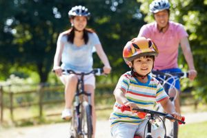 Image of a family happily riding bikes outside because they've recently been to their ear, nose and throat doctor