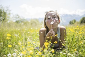 Image of a woman blowing a dandelion before the allergy testing begins