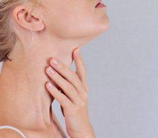 Image of a woman with her hand on her neck and worrying if she may have head and neck cancer