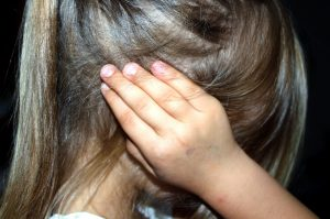 Image of child with her hand over her ear in need of an ear doctor