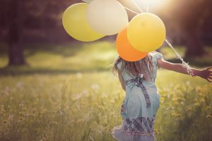 Image of a girl running with balloons hoping she does not have skin allergies and needs testing